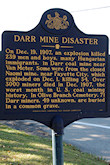 "The plaque reads as follows: ""On December 19, 1907, an explosion killed 239 men and boys, many Hungarian immigrants, in Darr coal mine near Van Meter. Some were from the closed Naomi mine near Fayette City, which exploded on Dec. 1, killing 34. Over 3000 miners died in Dec. 1907, the worst month in U. S. coal mining history. In Olive Branch Cemetery, 71 Darr miners, 49 unknown, are buried in a common grave."""